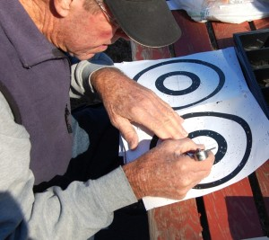 Bean measures to find which shot was closer to the bullseye during the fall Turkery Shoot.