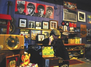Kevin Scoggin, owner of Crossroads, talks on the phone inside his music store. He said he had collected 10,000 records before he went into business and started selling them.