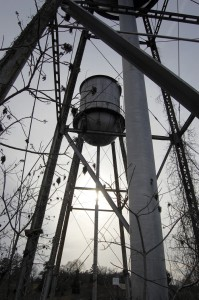 """The water tanks, which have the words """"N.C. Finishing Company"""" on them, rise above the debris at the former Color-Tex plant site."""