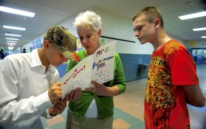 West Rowan Middle School Principal Nancy Barkemeyer, center, lets A.J. Wight and Lucas Lemly read her handmade going-away card on the last day of school. Barkemeyer is the Rowan-Salisbury School System principal of the year.  Jon C. Lakey/Salisbury Post