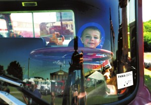 At the NC Transportation Museum's first firetruck show, 4-year-old Landon Hoopaugh from Mt. Pleasant gets to sit behind the wheel of a 1973 Mack firetruck from the Troy Volunteer Fire Department in Montgomery County. The windshield of the truck is reflecting some other trucks and buildings at the museum. photo by Wayne Hinshaw, for the Salisbury Post