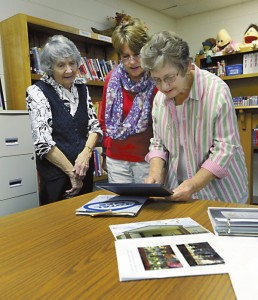 Charter members Doris Straub, Betsy Safrit and Sadie Phillips look over old photos from the history of the church.  Photo by Wayne Hinshaw, for the Salisbury Post