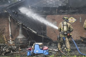 Josh Bergeron / Salisbury Post - A firefighter puts out remaining hot sections of a fire in Granite Quarry on Friday. The house was declared a total loss. No one was hurt in the fire.