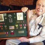J.L. Horton holds a framed collection of his and wife Hilda's World War ll medals. Photo by David Freeze