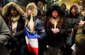 """People attend a vigil outside the French consulate in Montreal, Friday, Nov. 13, 2015. Canadian Prime Minister Justin Trudeau offered """"all of Canada's support"""" to France on Friday night in the wake of """"deeply worrying"""" terrorist attacks in Paris that killed at least 120 people. (Graham Hughes/The Canadian Press via AP)"""