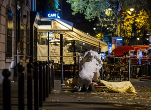 Investigating police officers inspect the lifeless body of a victim of a shooting attack  outside the Bataclan concert hall in Paris, France, Friday, Nov. 13, 2015. Well over 100 people were killed in Paris on Friday night in a series of shooting, explosions. French President Francois Hollande declared a state of emergency and announced that he was closing the country's borders. (AP Photo/Kamil Zihnioglu)