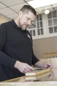 Josh Bergeron / Salisbury Post - Scott Whittington, who runs USA Made Blade with his business partner Kevin O'Mellan, sharpens his knife Thursday at the company's new storefront on North Main Street in Salisbury. USA Made Blade will have a grand opening for its new business on Saturday.