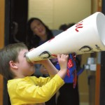August tries out the megaphone as a telescope. Wayne Hinshaw/For the Salisbury Post