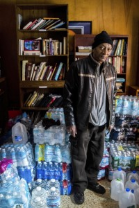 Flint, Mich., resident Michael Simmons, 61, stands amongst gallons and cases of bottled water as he arrives to pick up free water from Pastor Bobby Jackson after Detroit-area volunteers dropped off more than 500 cases on Saturday.  (Jake May/The Flint Journal-MLive.com via AP)