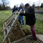 Post member Leonard Hall, Salisbury Councilman Kenny Hardin and DeCarlo Duling lift up a wooden cover that the Post members put down over a washed out area around a storm grate. Jon C. Lakey/Salisbury Post