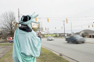 Josh Bergeron / Salisbury Post - Cars whiz by Livingstone College student Tonaka Phillips on Thursday as he plays a trombone while dressed in a Statue of Liberty outfit.