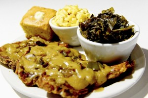 Smothered pork chops with sides of cornbread, macaroni and cheese and greens at Carmi Soul Food in Pittsburgh. (Pam Panchak/Pittsburgh Post-Gazette/TNS)