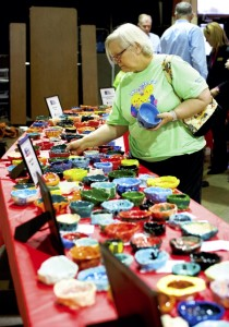 ALLISON LEE ISLEY/SALISBURY POST Pat Wayne looks through the various pottery bowls crafted by students for the Empty Bowls Fundraiser at North Hills Christian School in Salisbury N.C. on Thursday, March 10, 2016.  The proceeds of the event go to Rowan Helping Ministries.