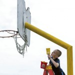 Blake Earley applies a coat of fresh paint to the one of the four basketball goals on the playground at Granite Quarry Elementary School. Jon C. Lakey/Salisbury Post