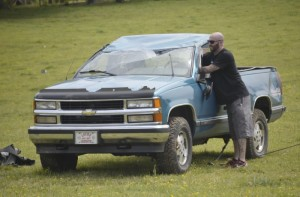 A tow truck driver adjusts the steering wheel of this Chevrolet Silverado after the driver, Raymond Crouse, crashed into a cow field in the 5100 block of Mooresville Road. He walked away with scratches. Shavonne Walker/Salisbury Post