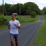 Pierre Lantuas carries the Peace Run torch along Old U.S. 70 Tuesday afternoon in Rowan County, on the way to Mooresville and, later, Charlotte. Mark Wineka/Salisbury Post