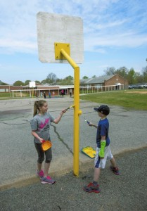 Teagan Johnson and Anders Thompson work together to apply new paint to the basketball goals at Granite Quarry Elementary School.  Jon C. Lakey/Salisbury Post