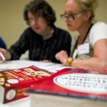 David Schroeder and Kelly Freeze check the scores submitted by the teams during the Scrabble Scramble on Tuesday.  Allison Lee Isley/Salisbury Post