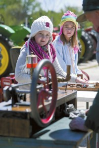 JON C. LAKEY / SALISBURY POST Cousins Sarah Waller and Fiona Raymer look up from the table of puzzles to watch Ron Green start his replicia of a 1893 Henry Ford engine.  The Antique Tractor show was held on Saturday afternoon at the North Carolina Transportation Museum. Saturday, April 9, 2016, in Spencer, N.C.