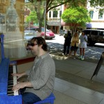 Clarence Marlin, Maia Smith and Mary James stand by the street listening to blind musician Randy Gilkey sing and play one of the downtown pianos Monday in Salisbury. Mark Wineka/Salisbury Post