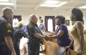 Rowan deputies Tim Cook and John Howard speak with the sisters of Gary Baldwin who they and five other deputies helpd after he suffered a heart attack in court. The sisters, Phyllis Shipp and Edith Boyd, attended a ceremony Thursday to honor the officers. Shavonne Walker/Salisbury Post