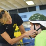 Mary Rosser with the Pedal Factory helps fit a helmet on Danni Moore. Powles Staton Funeral Home in Rockwell donated 60 bicycle helmets to the Rowan County Sheriff's Office's Youth Leadership Camp. Tuesday morning, the 28 campers involved in the program's July session learned about bicycle safety. Rebecca Rider/Salisbury Post