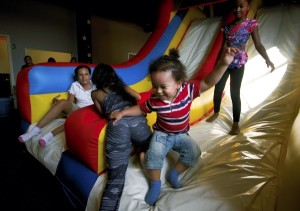 "Yazan Gordon, 2, comes down a slide on one of the inflatables at Bounce City on Friday during the  ""Come in Unity with the Community"" event.  Jon C. Lakey/Salisbury Post"