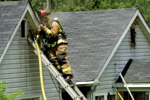 JON C. LAKEY / SALISBURY POST South Salisbury firefighter uses a ladder to access the attic with a hose line.  Several fire departments responded to a structure fire in the 1400 block of Pine Ridge Road on Thursday.