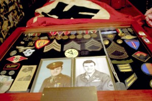 Mark Wineka/Salisbury Post   Staley Johnson holds photos, medals patches, dog tags and even Nazi soldier items he collected during his 83rd Infantry Division's march toward Germany from June 1944 to May 1945. Among the items are his Purple Heart and Bronze Star. He yanked the Nazi flag at back off a flagpole of a German building during the Allied Forces march toward Berlin.