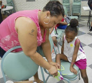 Amanda Raymond/Salisbury Post Anitra Kelly helped her daughter Aubriana find new shoes for the school year at Gethsemane Missionary Baptist Church's back-to-school giveaway on Saturday.
