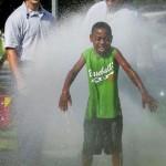 Tyler Ellis, 9, enjoys the cool water provided by Capt. Shawn McBride, Engineer Brantley Shanks and Firefighter Tony Amenta of the Salisbury Fire Department. Jon C. Lakey/Salisbury Post