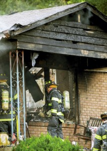 Firefighters get a closer look at the house that burned on East Centerview Street, China Grove, on Friday.  Jon C. Lakey/Salisbury Post