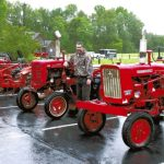 """On a rain-soaked Saturday afternoon before the Grace Lutheran Church fish fry, Chris Sloop stands next to the Farmall tractor that once belonged to his late grandfather, Robert """"Tip"""" Sloop. It's in a line of eight tractors, each owned at one time by a different Sloop brother.   Mark Wineka/Salisbury Post"""