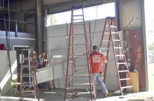 Russell Johnson, left, and Jeremy Chase, both of Perry's Overhead Doors hang a new automatic garage door at the East Spencer fire station. The repairs are being done to make room so that a future truck will fit into the station. Shavonne Walker/Salisbury Post