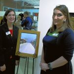 Kyna Grubb, executive director of Rowan Helping Ministries, stands with artist Rebecca Little, right, and Little's 'Christmas on the Square' oil painting from which this year's Christmas Honor Card is taken. Mark Wineka/Salisbury Post