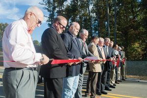 Josh Bergeron / Salisbury Post - A gaggle of public officials cut a ribbon at the border between Landis and China Grove for the opening of a new underpass on Kimball Road.