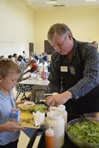 Randy Cox, a Master Gardener who runs the 4-H club at Sacred Heart Catholic School, helps a student get salad dressing for his side salad — which was grown in the school garden. Rebecca Rider/Salisbury Post