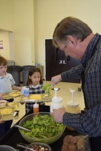 Randy Cox, a Master Gardener who runs Sacred Heart's 4-H Club, dishes out salad during lunch Friday. The lettuce and many of the salad toppings were grown by students. Rebecca Rider/Salisbury Post