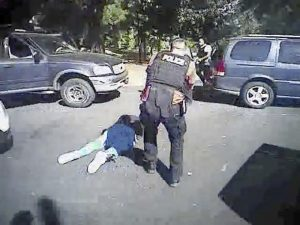 FILE - This image made from video provided by the Charlotte-Mecklenburg Police Department on Saturday, Sept. 24, 2016 shows Keith Scott on the ground as police approach him in Charlotte, N.C., on Sept. 20, 2016.   Charlotte-Mecklenburg District Attorney Andrew Murray announced Wednesday, Nov. 30, 2016, that the shooting by officer Brent Vinson was justified.  Vinson, who is black, shot and killed Keith Lamont Scott on Sept. 20.  (Charlotte-Mecklenburg Police Department via AP)