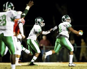 Kannapolis linebacker Steven Howie (2) begins congratulating his teammate Elijah Hall as he carries the ball to the end zone in the second round of playoffs against Davie on Friday night, Nov. 25, 2016 at Davie County High School in Mocksville, N.C. The War Eagles won the game, 38-19. (Winston-Salem Journal/Allison Lee Isley)
