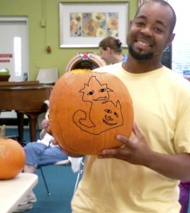 Submitted photo Kendall White holds a pumpkin he tried to sketch a design on at Trinity Oaks.