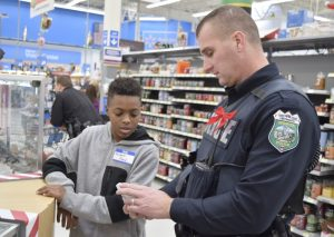 """Robert, left, a student at Knox Middle, and officer J.M. Reep, right, examine a watch at Walmart. Robert is one of the students who participated in local law enforcement's """"Shop with a Cop"""" Thursday morning. Students were allowed to spend $50 on themselves, but were asked to use the remaining $50 to purchase gifts for family members. Robert was looking for a present for his father. Rebecca Rider/Salisbury Post"""