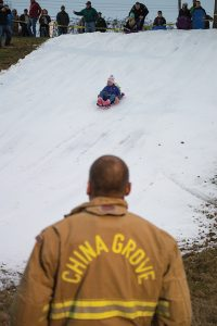 Josh Bergeron / Salisbury Post - A China Grove firefighter looks on at children slide down a slab of fake snow on Saturday during the town's annual Christmas in the Grove event.