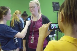 Lauren Arnold shoots video as Katherine Peeler, left, interviews first grade teacher Kristen Smith, right, about her class's experience learning animation from Anthony Johnson's students. Rebecca Rider/Salisbury Post.