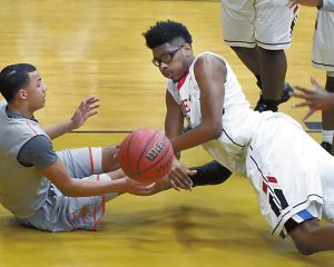 "Salisbury's Tre Oats ""0"" and Lexington's Adrian Craven (2) scramble for a loose ball.    photo by Wayne Hinshaw, for the Salisbury Post"