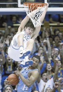 Duke's Grayson Allen hangs from the rim after a dunk as North Carolina's Kennedy Meeks (3) catches the ball during the second half of an NCAA college basketball game in Durham, N.C., Thursday, Feb. 9, 2017. Duke won 86-78. (AP Photo/Gerry Broome)