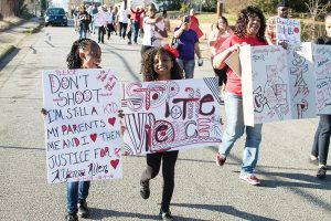 Josh Bergeron / Salisbury Post - Londyn Addison and Janiah Finger, at left, smile as they march in a Community Speaks march on Saturday. The march advocated for an end to local giolence.