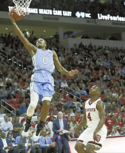 North Carolina's Nate Britt (0) drives to the basket against North Carolina State's Dennis Smith Jr. (4) during the second half of an NCAA college basketball game in Raleigh, N.C., Wednesday, Feb. 15, 2017. North Carolina won 97-73. (AP Photo/Gerry Broome)