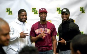 JON C. LAKEY / SALISBURY POST ... Javon Hargrave of the Pittsburgh Steelers (left),  and Chris Smith of the Jacksonville Jaguars (right), flank Zion DeBose.  North Rowan High school football standout Zion DeBose revealed to his family, friends and coaches were he is planning on attending college to continue his football career. On Friday with much fanfare DeBose took of his jacket to reveal a Virginia Tech t-shirt to the cheers of the crowds.  Friday, February 3, 2017, in Salisbury, N.C.